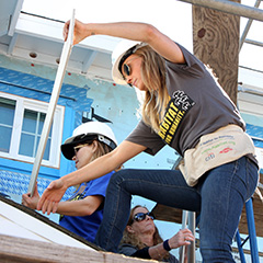 female volunteers helping build houses with other volunteers