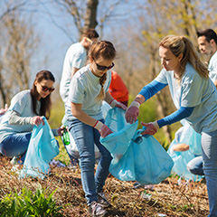 volunteer workers helping each other pick up trash in a park