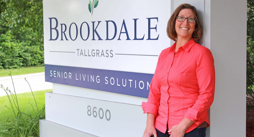 Janelle McGee stands next to Brookdale signage